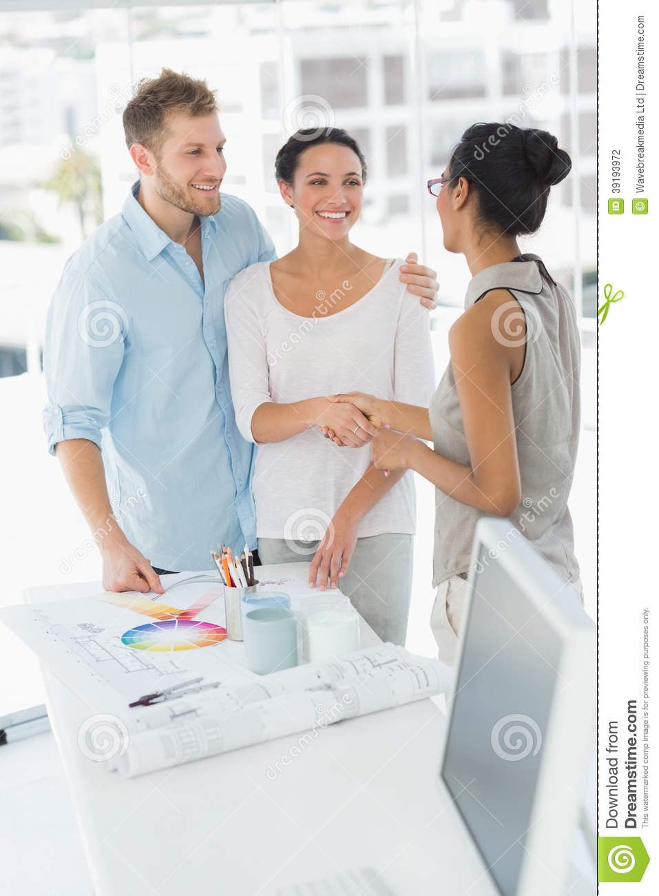 Interior Designer Shaking Hands With Smiling Client Stock