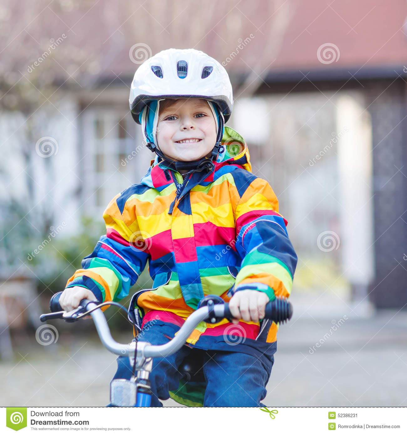 Kid Boy In Safety Helmet And Colorful Raincoat Riding Bike