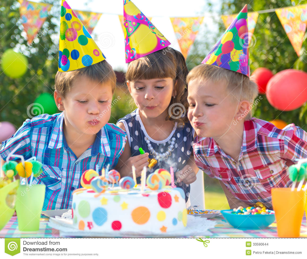Kids At Birthday Party Blowing Candles On Cake Stock