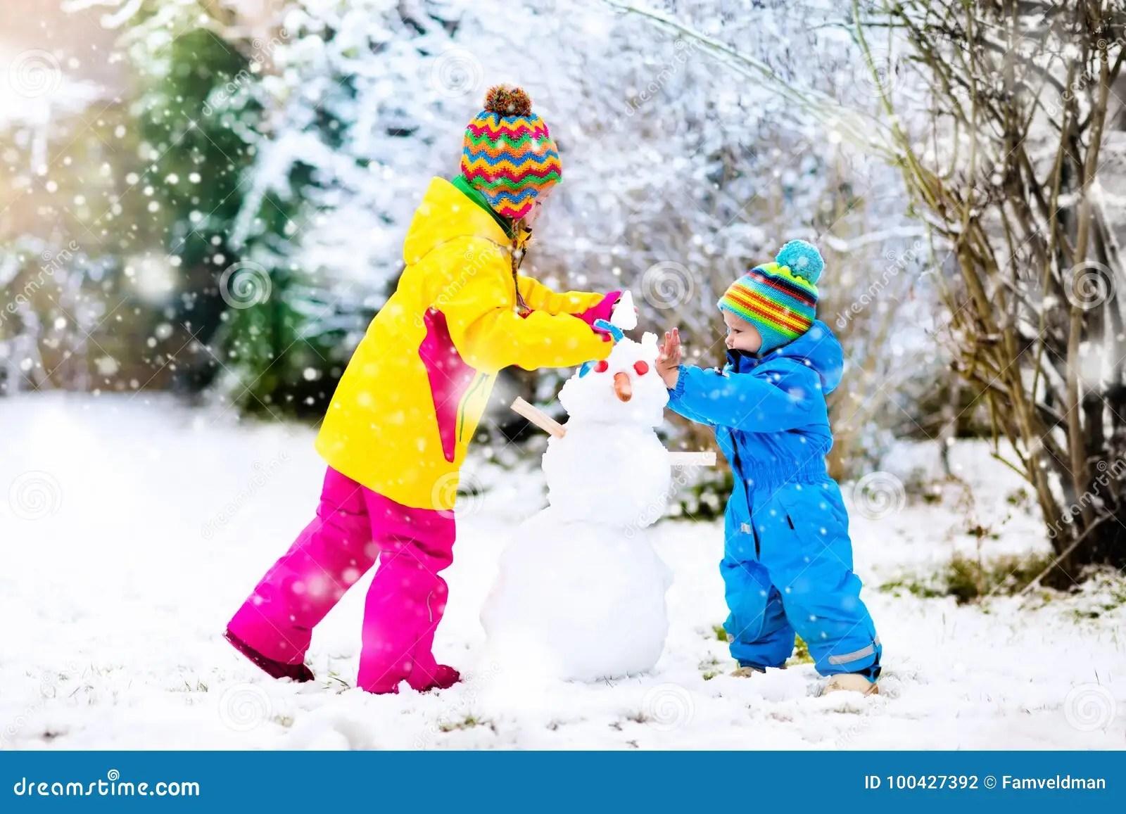 Kids Building Snowman Children In Snow Winter Fun Stock