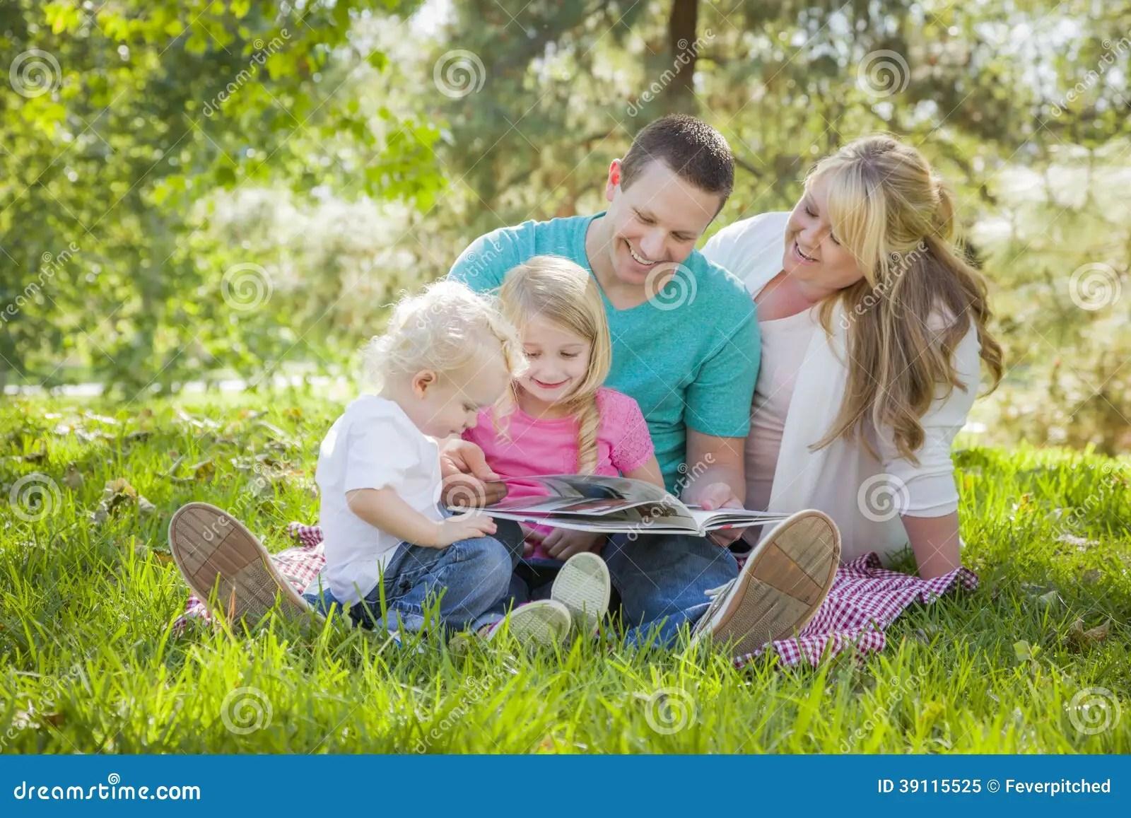 La Familia Joven Goza El Leer De Un Libro En El Parque