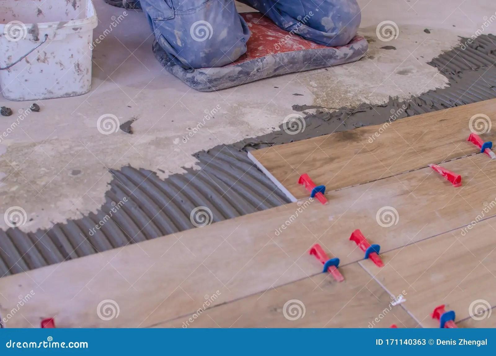 https www dreamstime com laying tile floor ceramic pressing down regulating installing plastic industrial crosses fixing professional worker image171140363