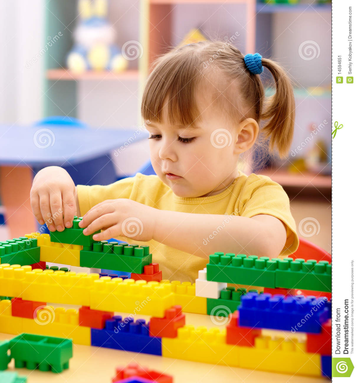 Little Girl Play With Building Bricks In Preschool Stock