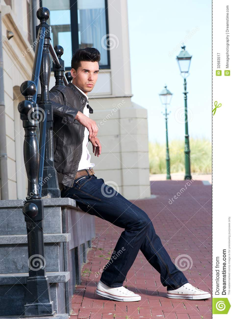 Male Fashion Model In Leather Jacket Sitting Outdoors