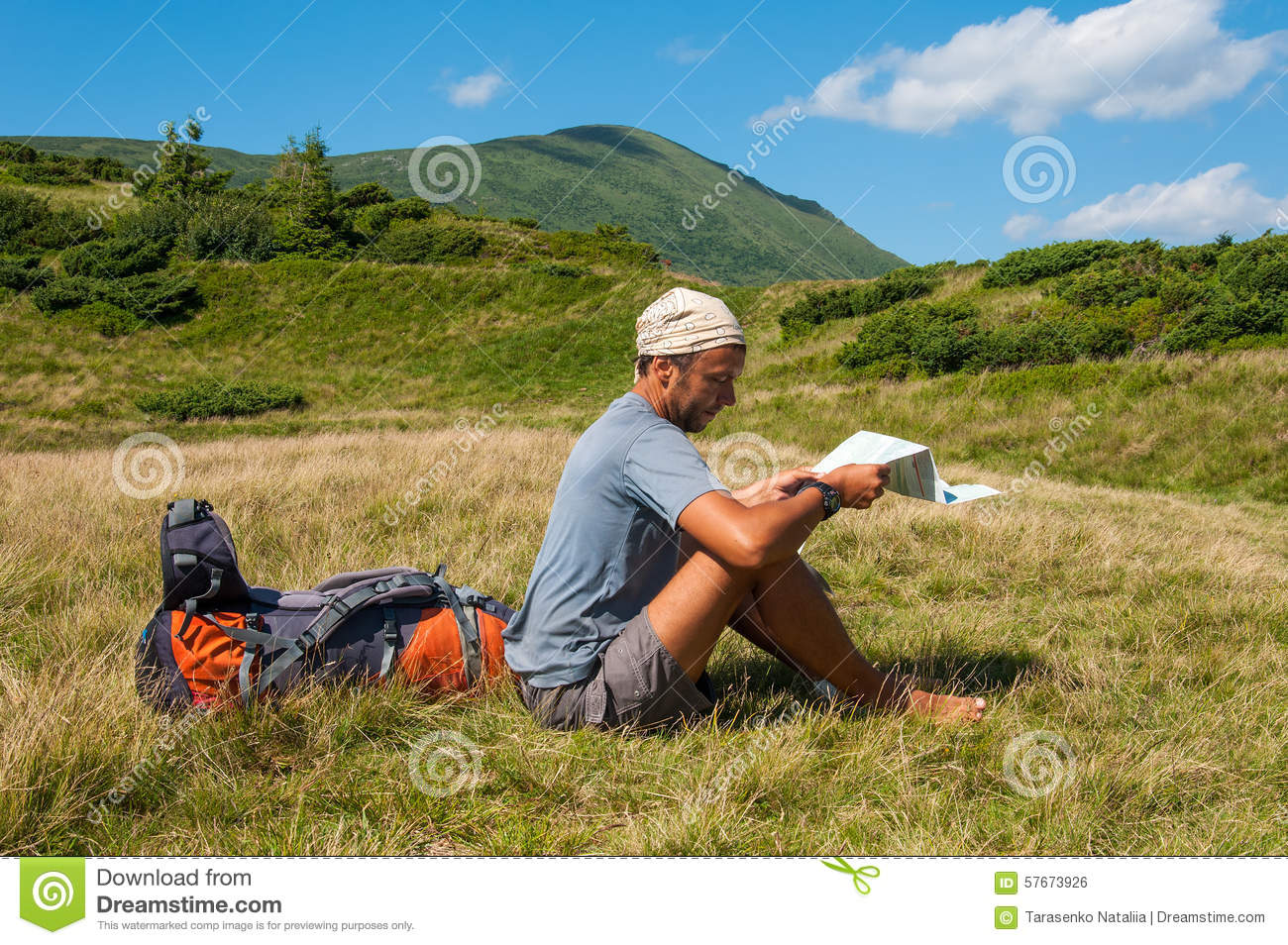 Man Tourist In Mountain Read The Map Stock Photo