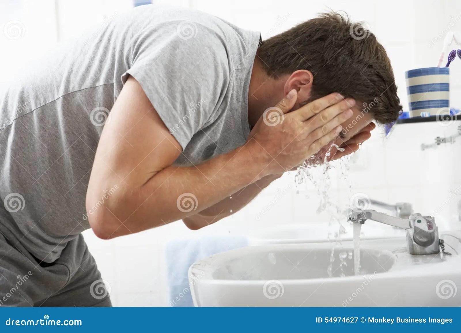 Man Washing Face In Bathroom Sink Stock Photo