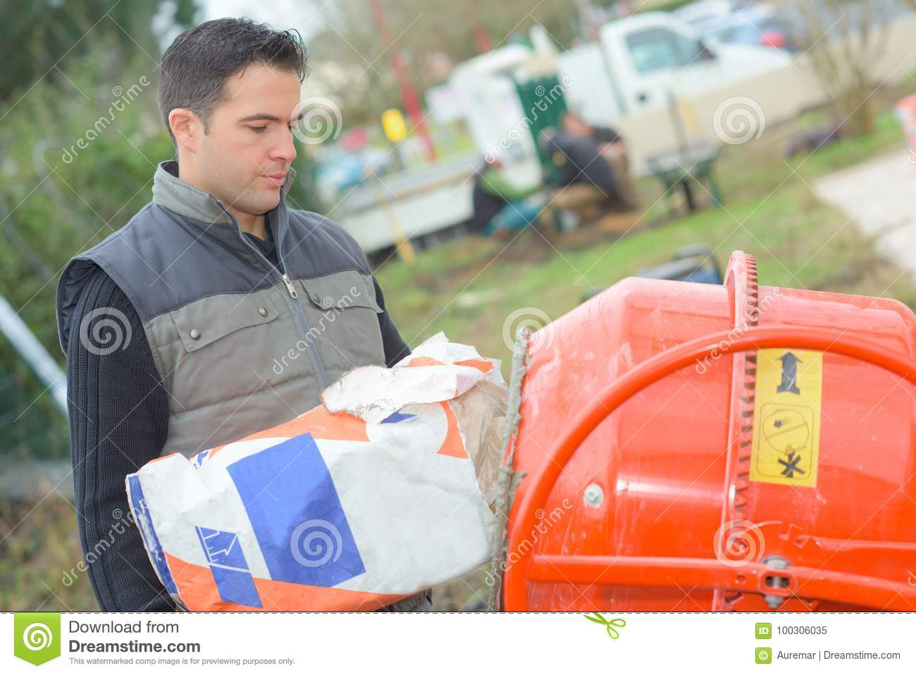 Mason Pouring Cement To Mixer Stock Image