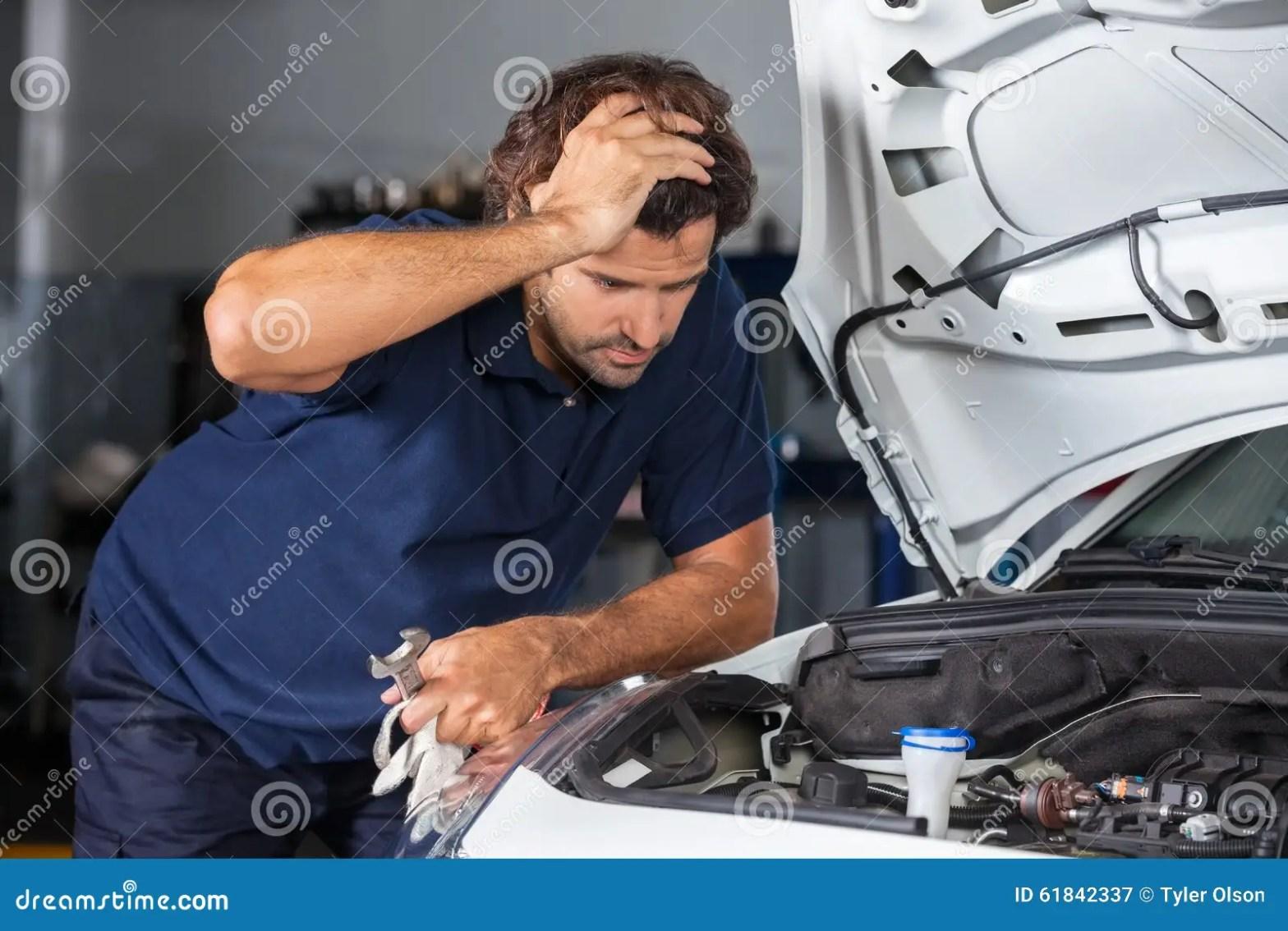 Mechanic Examining Car Engine At Repair Shop Stock Image