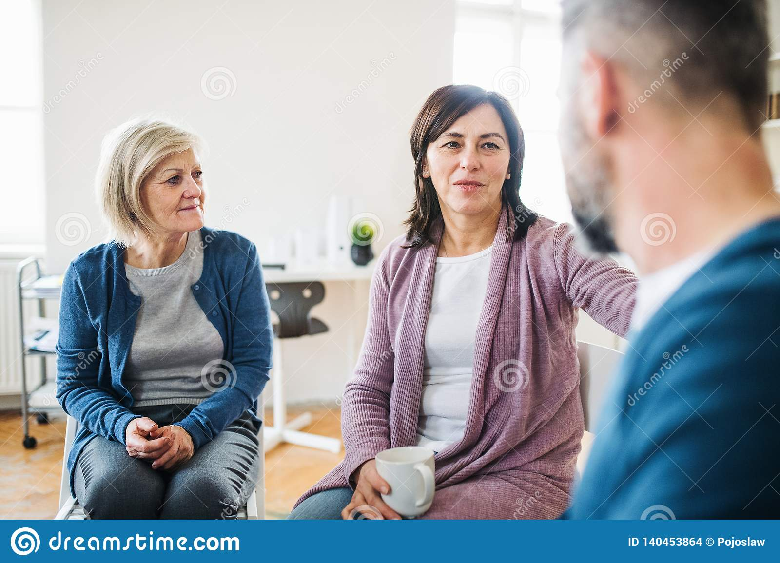 Men And Women Sitting In A Circle During Group Therapy