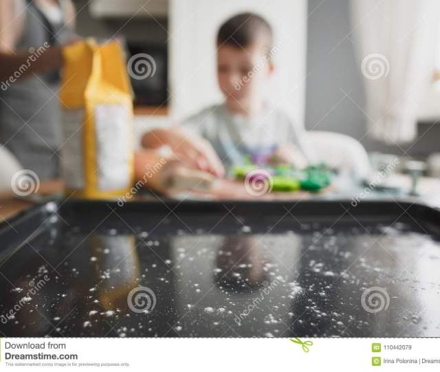 Mom And Her Son Cook Cookies In The Cozy Home Kitchen Black Baking Sheet Sprinkled With Flour Close Up