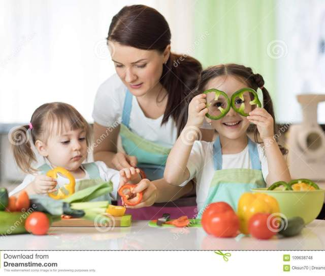 Mom Teaches Two Daughters To Cook At The Kitchen Table With Raw Food
