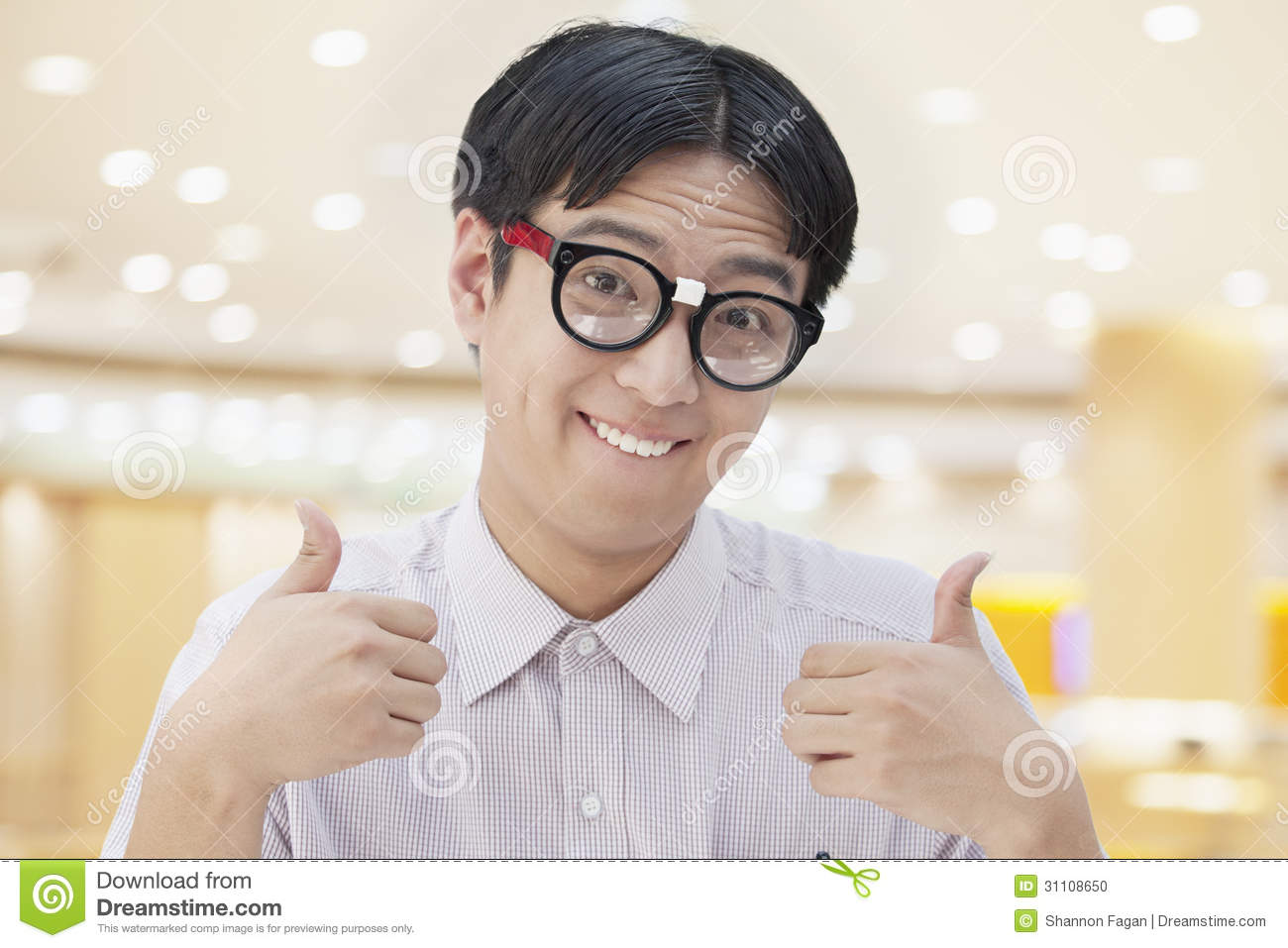 Nerdy Man With Glasses Giving Thumbs Up Looking At Camera
