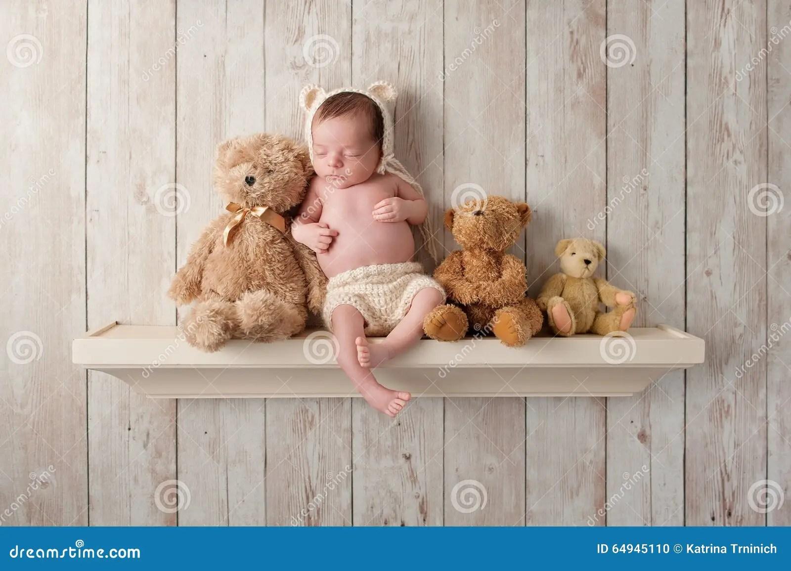 Newborn Baby Boy On A Shelf With Teddy Bears Stock Photo