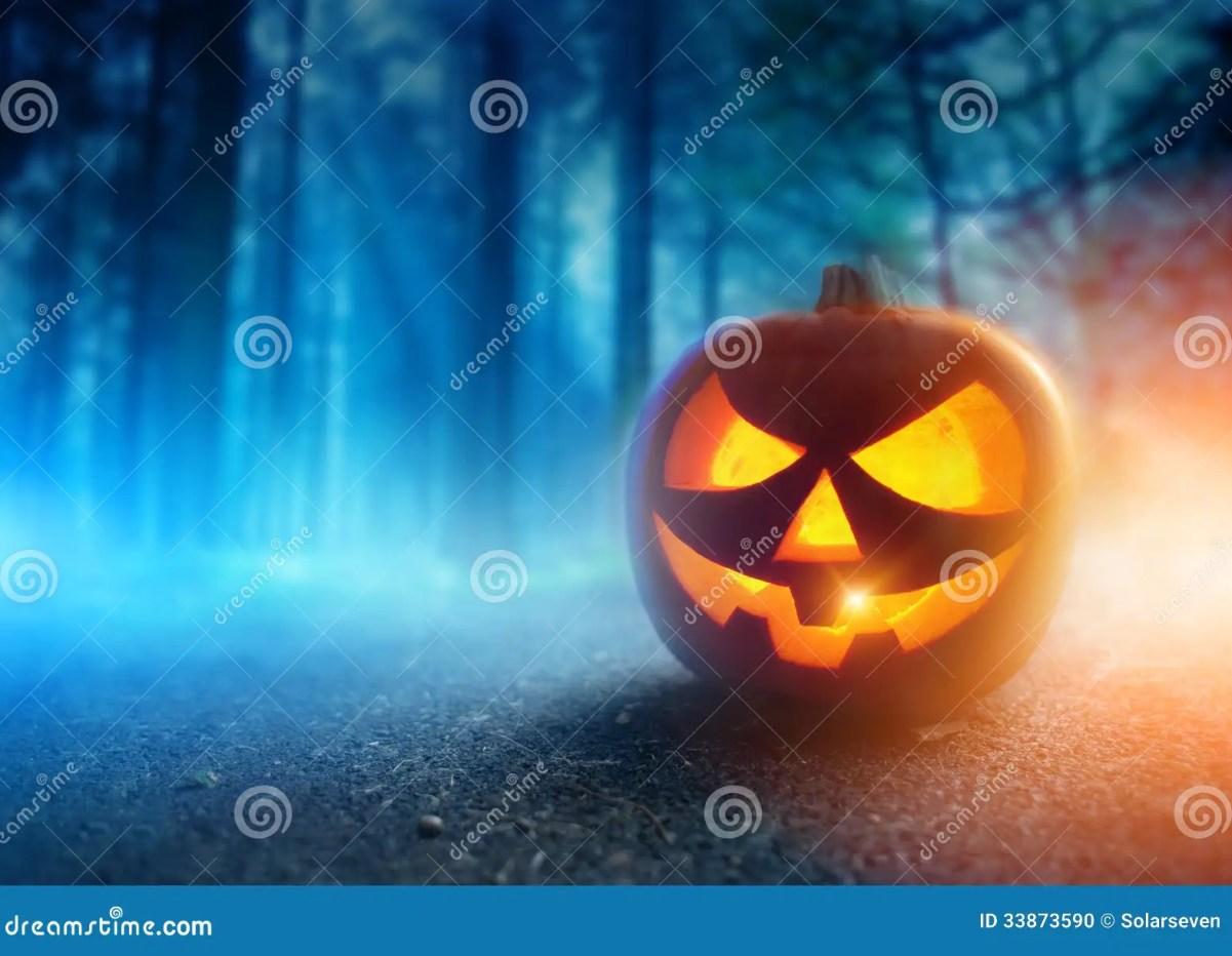 Une lanterne rougeoyante de Jack O dans la forêt de brume d'adark Halloween… © Solarseven | Dreamstime