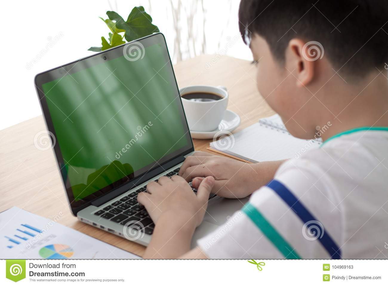 Over The Shoulder Shot Of An Asain Boy Typing On A