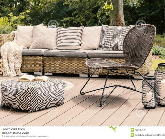 Patterned Pouf And Rattan Chair On Wooden Patio With Pillows On