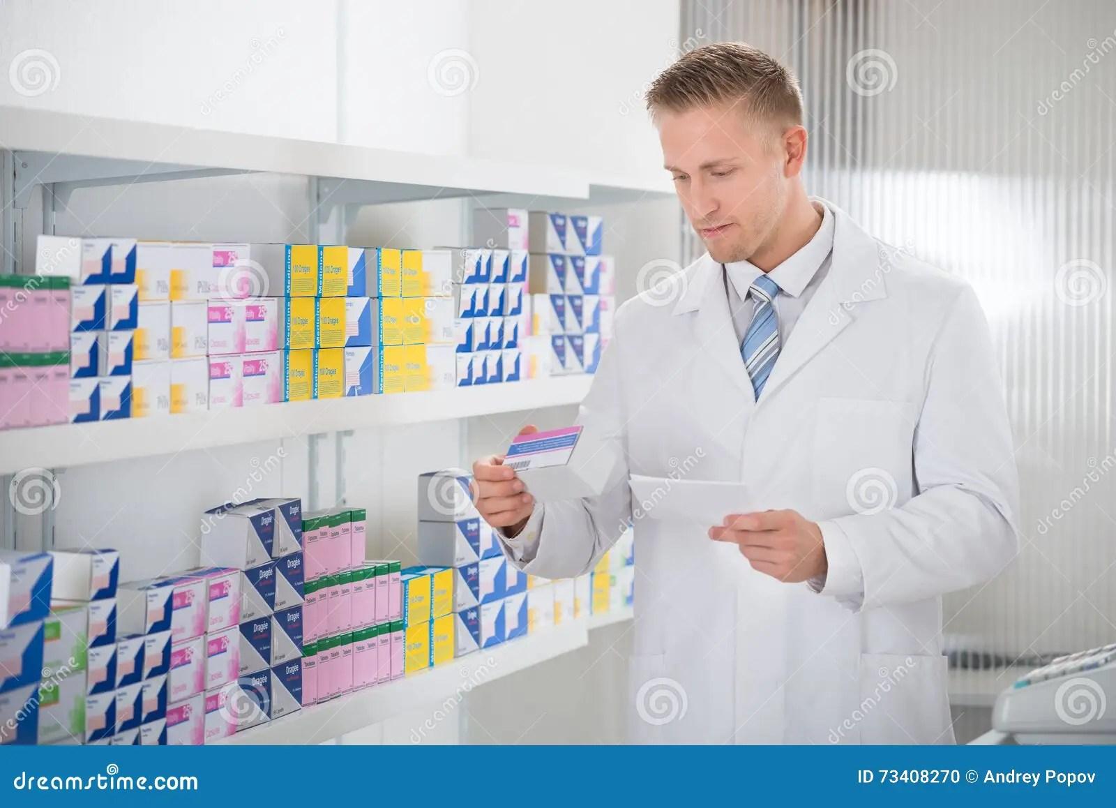 Pharmacist Reading Label On Medicine Stock Photo