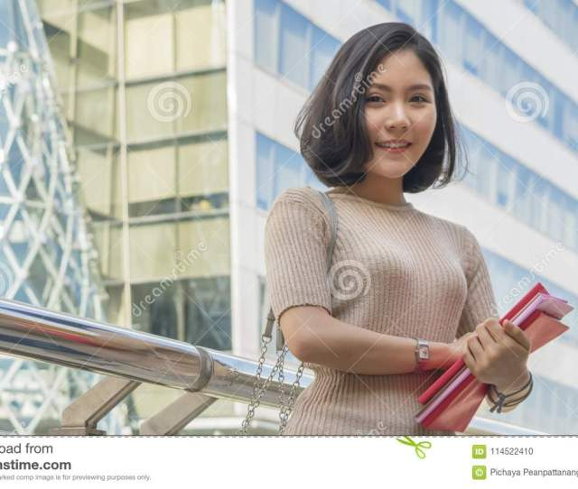 Portrait Of Asian Teen Girl Holds Red Book Stands And Dresses Up