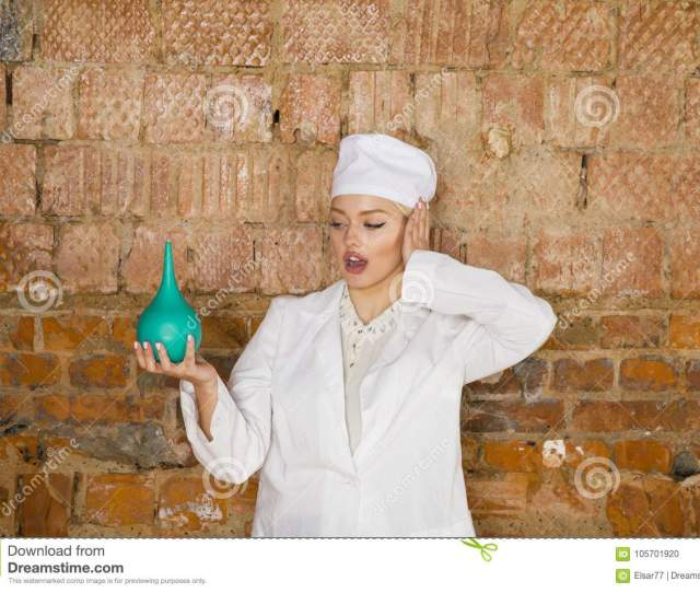 Portrait Of A Good Looking Young Nurse With Enema In Her Arms In A Brick Red Background