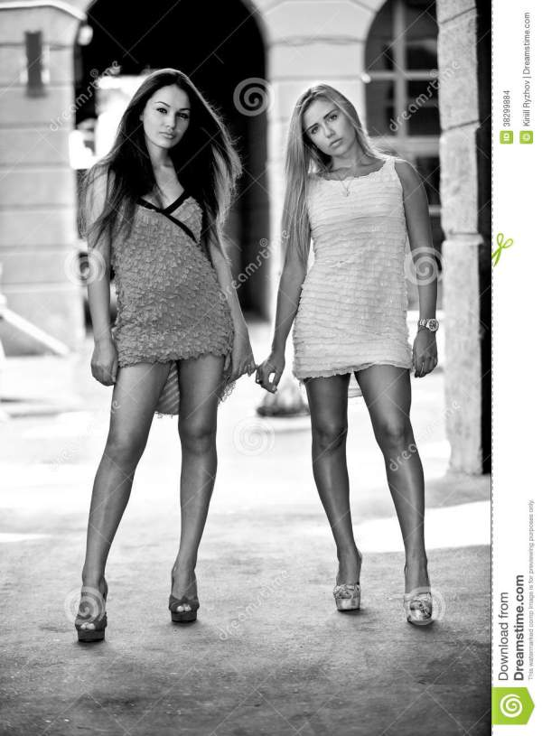Portrait Of Two Sexy Girls Standing On Street Holding ...