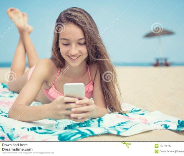 Pretty Teenager Girl Using A Smart Phone Lying On The Beach With The Sea And Horizon