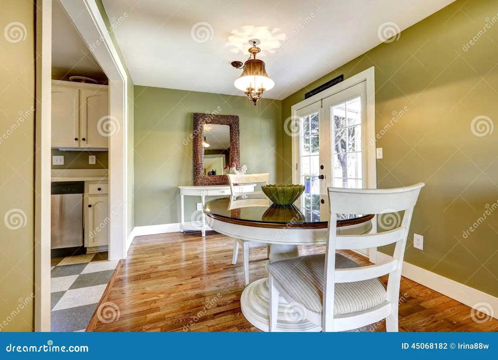 la table de salle a manger a place dans la chambre avec le mur vert et la porte francaise blanche