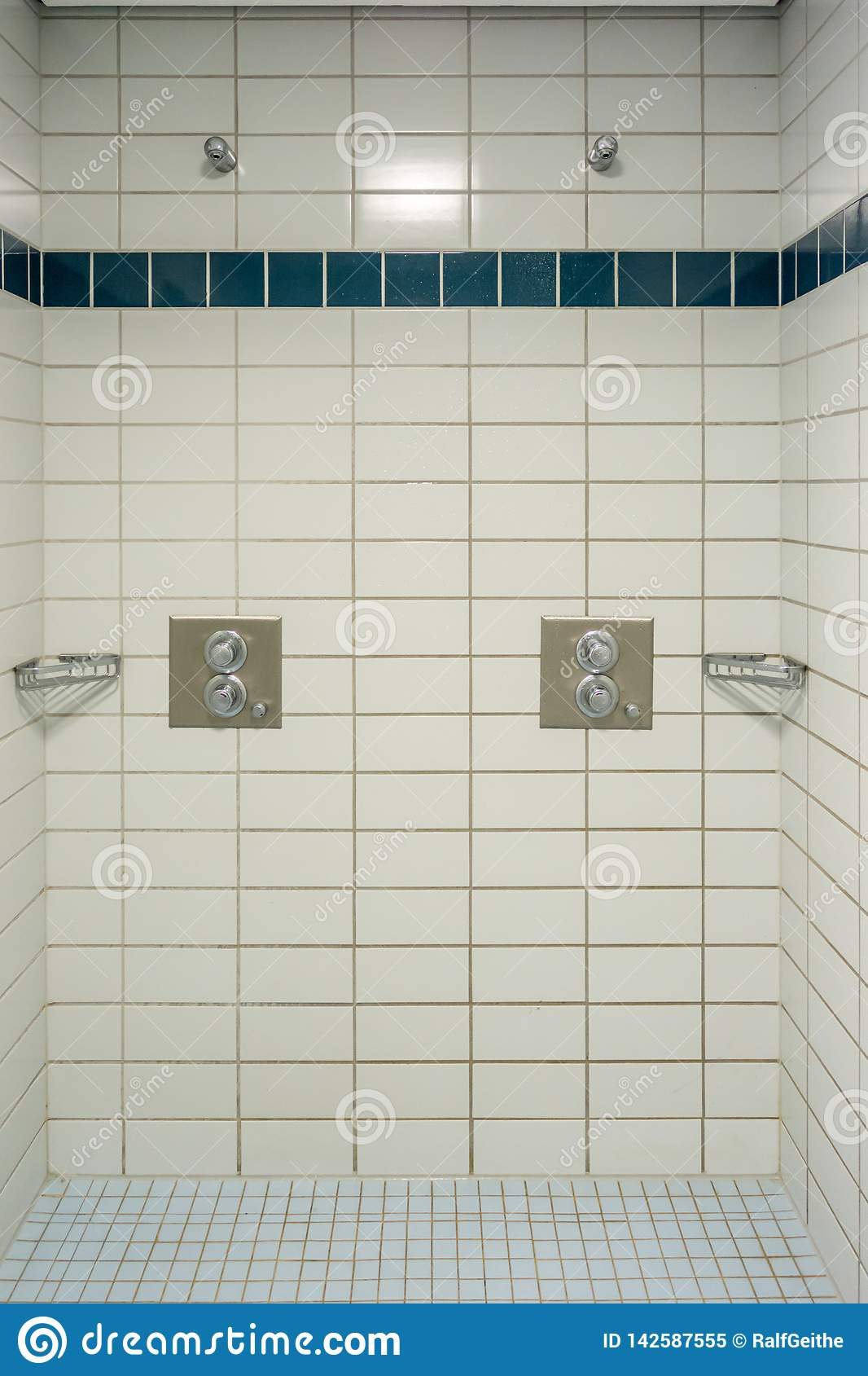 several showers in a fully tiled shower