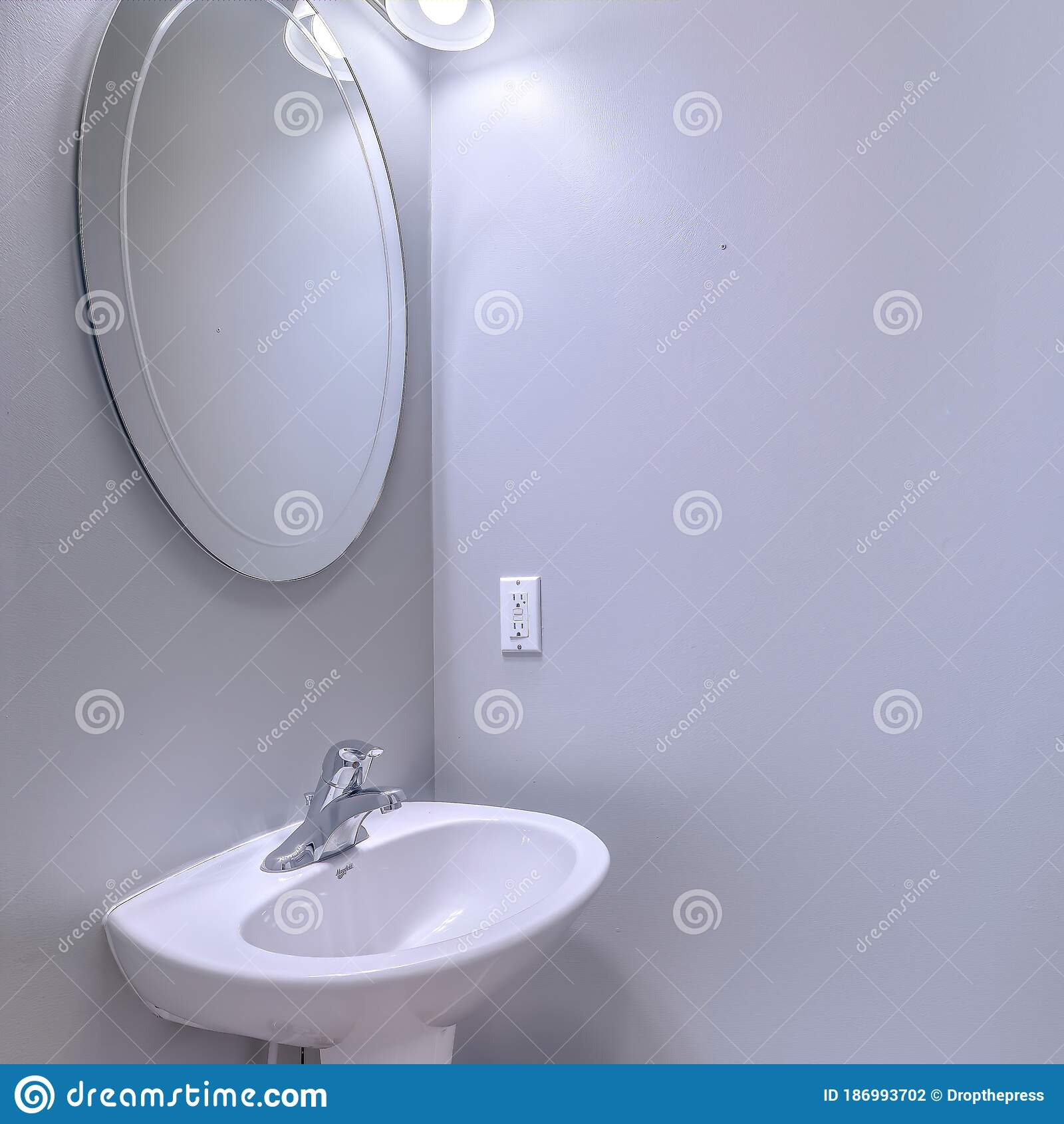 square bathroom interior with wall light and oval mirror over stand alone pedestal sink stock photo image of architectural toilat 186993702