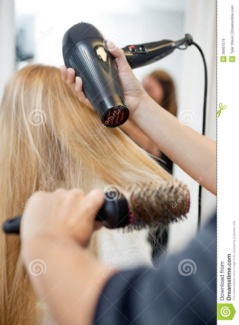 Stylist Drying Womans Hair In Hairdresser Salon Stock