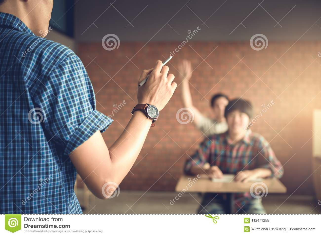 Teacher Asking Questions And Student Raising Hands To