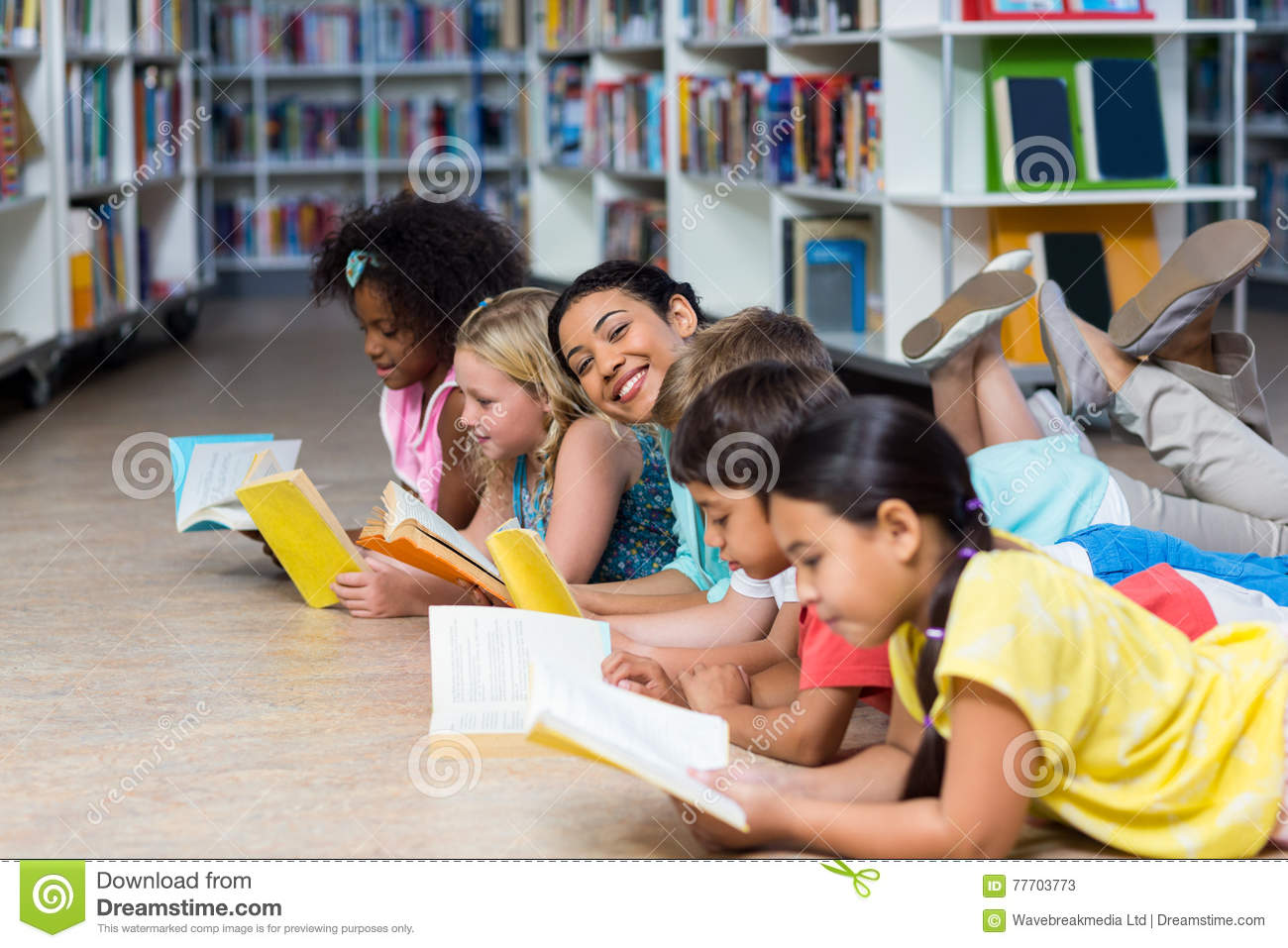 Teacher With Children Lying Down While Reading Books Stock