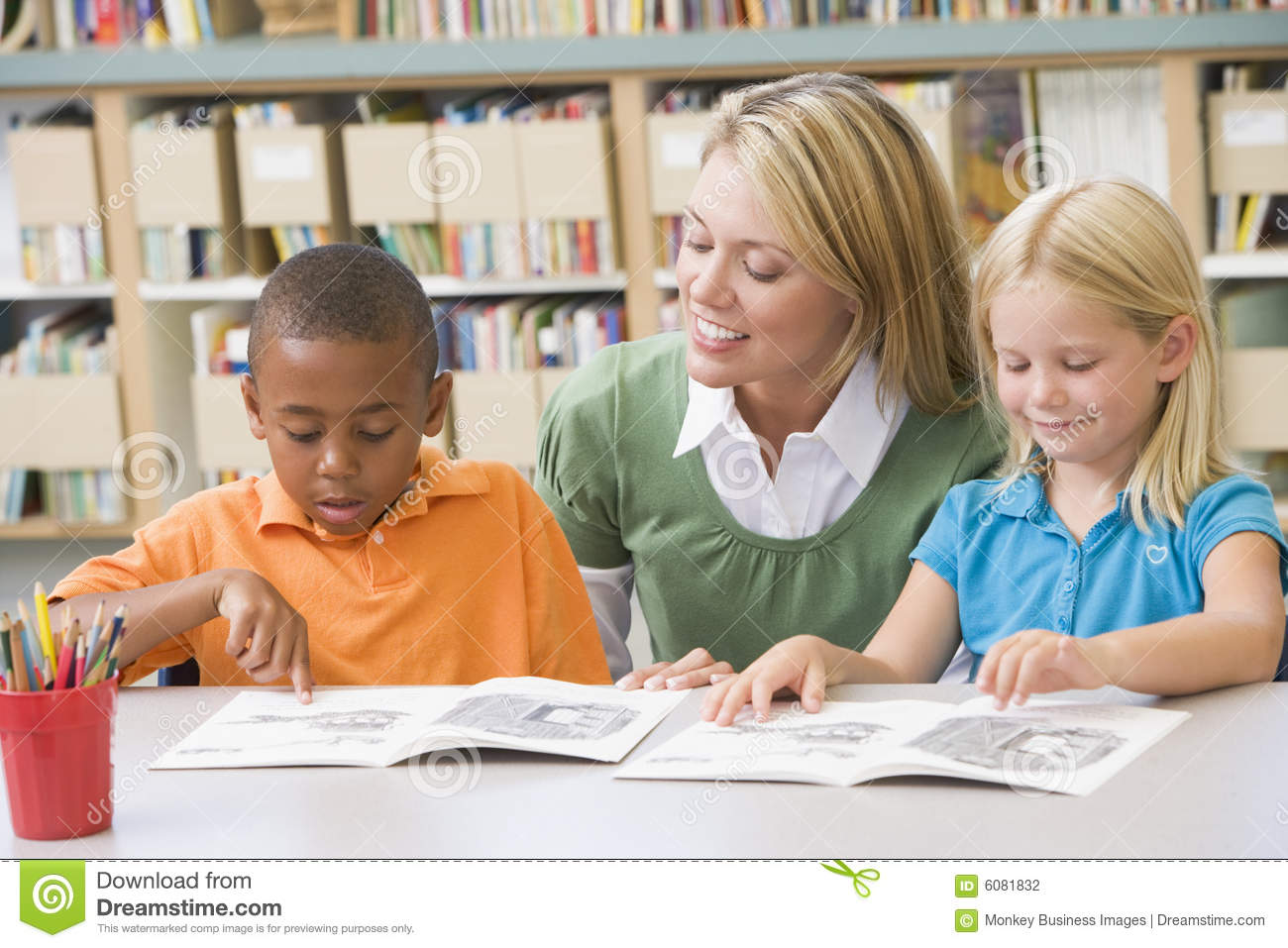 Teacher Helping Students With Reading Skills Stock Photo