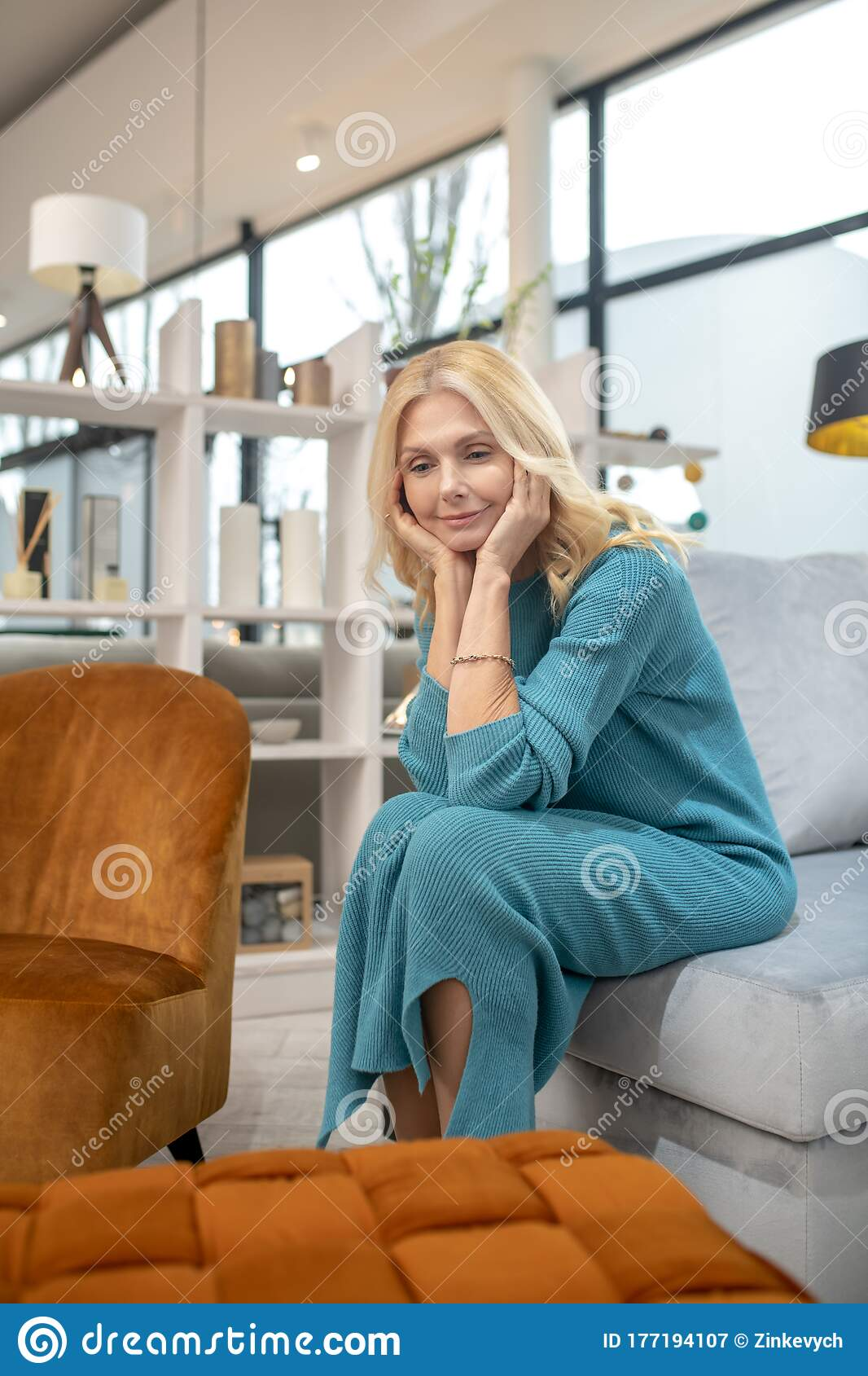 Blonde Woman In A Blue Dress Sitting On A Sofa Stock Image Image Of Female Store 177194107