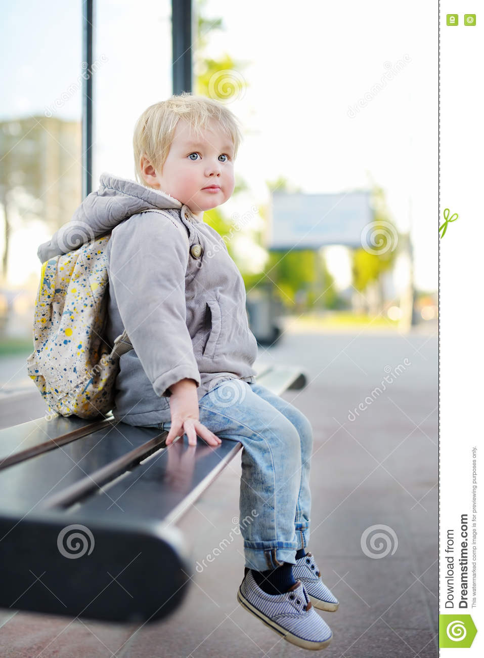 Toddler Boy Sitting On Bench On Bus Stop Stock Photo