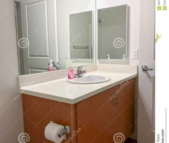 A Very Simple Portion Of A Residential Bathroom With Wood Vanity Toilet Paper Sink Hand Soap Mirrors And Medicine Chest Bathroom Is Clean And Plain