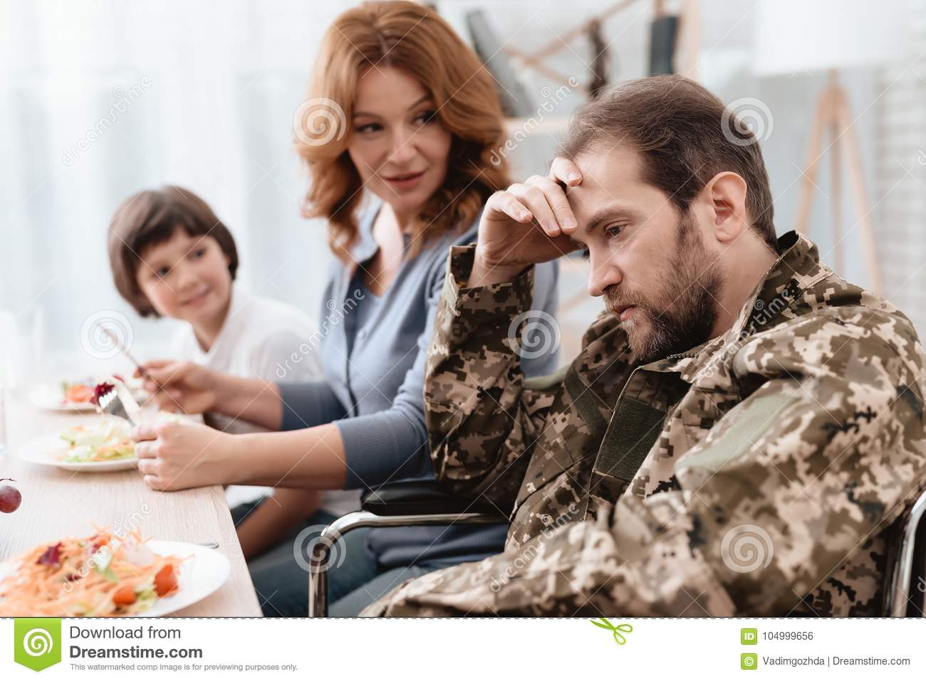 A Veteran In A Wheelchair Dines With His Family A Man In