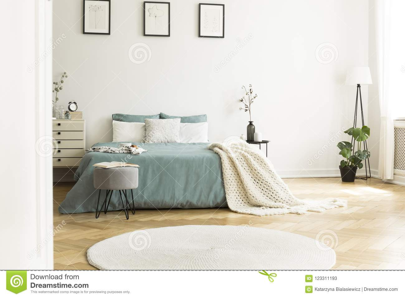 White Round Rug In Front Of Green Bed With Blanket In