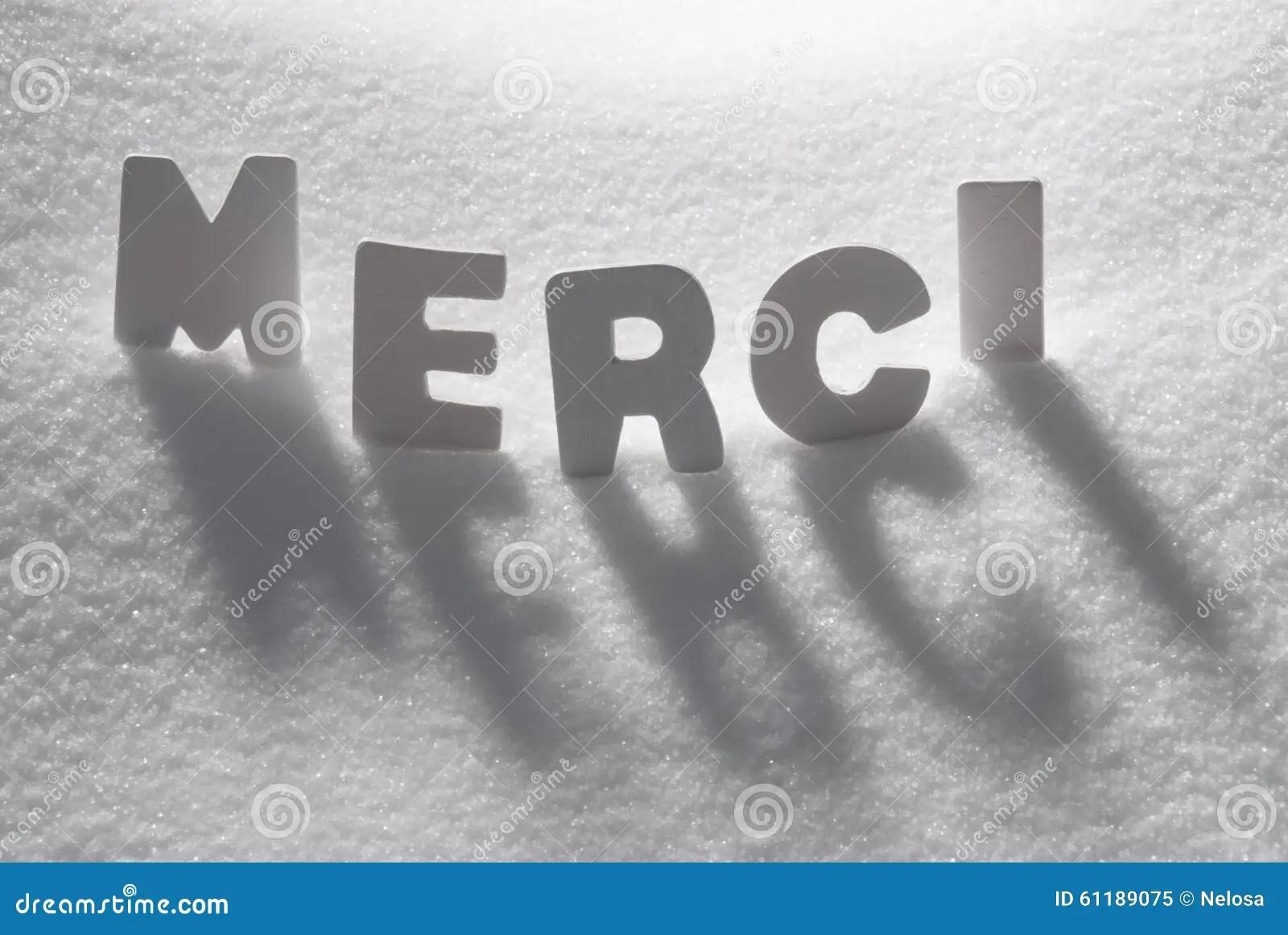White Word Merci Means Thank You On Snow Stock Photo