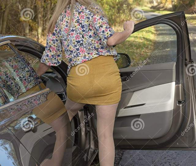 Blond Woman Motorist Wearing A Tight Skirt Getting Into The Drivers Seat Of A Saloon Car