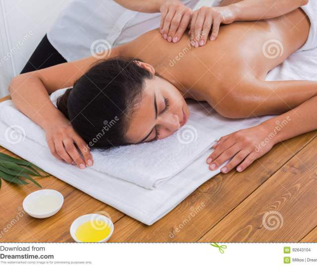 Spa Back Massage Therapy Masseur Make Body Oil Massage To Beautiful Indian Girl In Cosmetology Cabinet Or Beauty Parlor