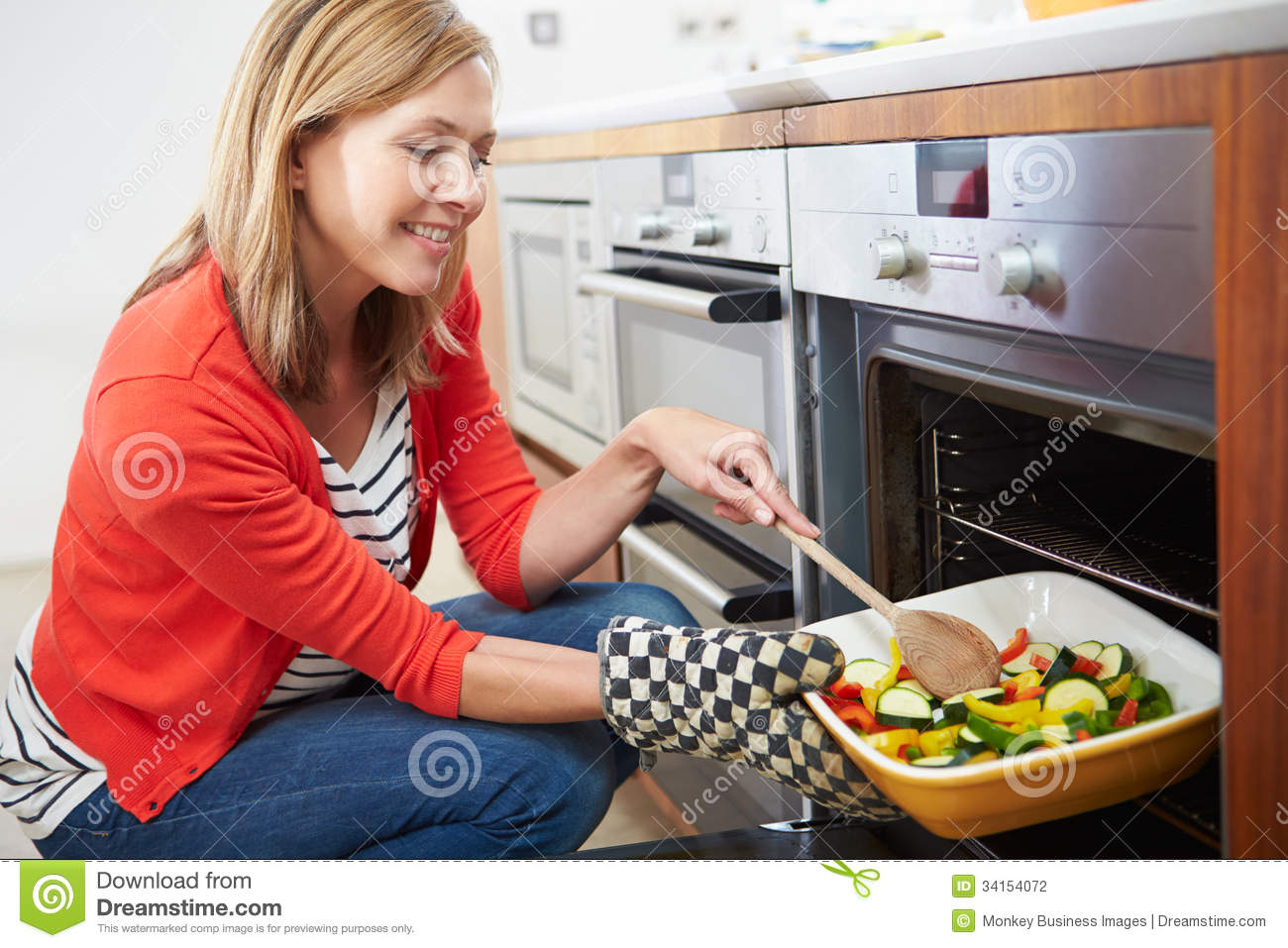 Woman Putting Tray Of Roast Vegetables Into Oven Stock