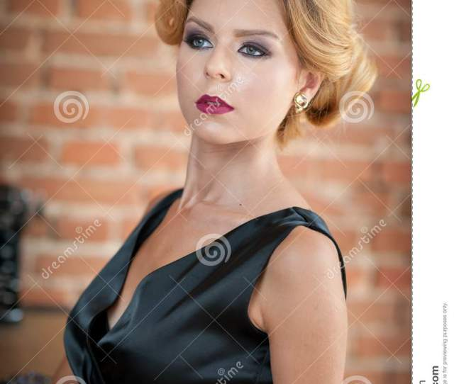 Young Beautiful Short Hair Blonde Woman In Black Dress Posing Elegant Romantic Mysterious Lady With Movie Star Look Bricks Wall On Background