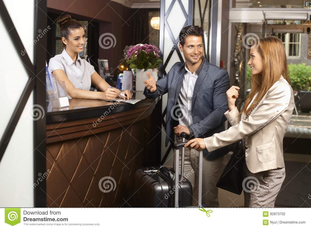 Young Couple At Hotel Reception Stock Photo