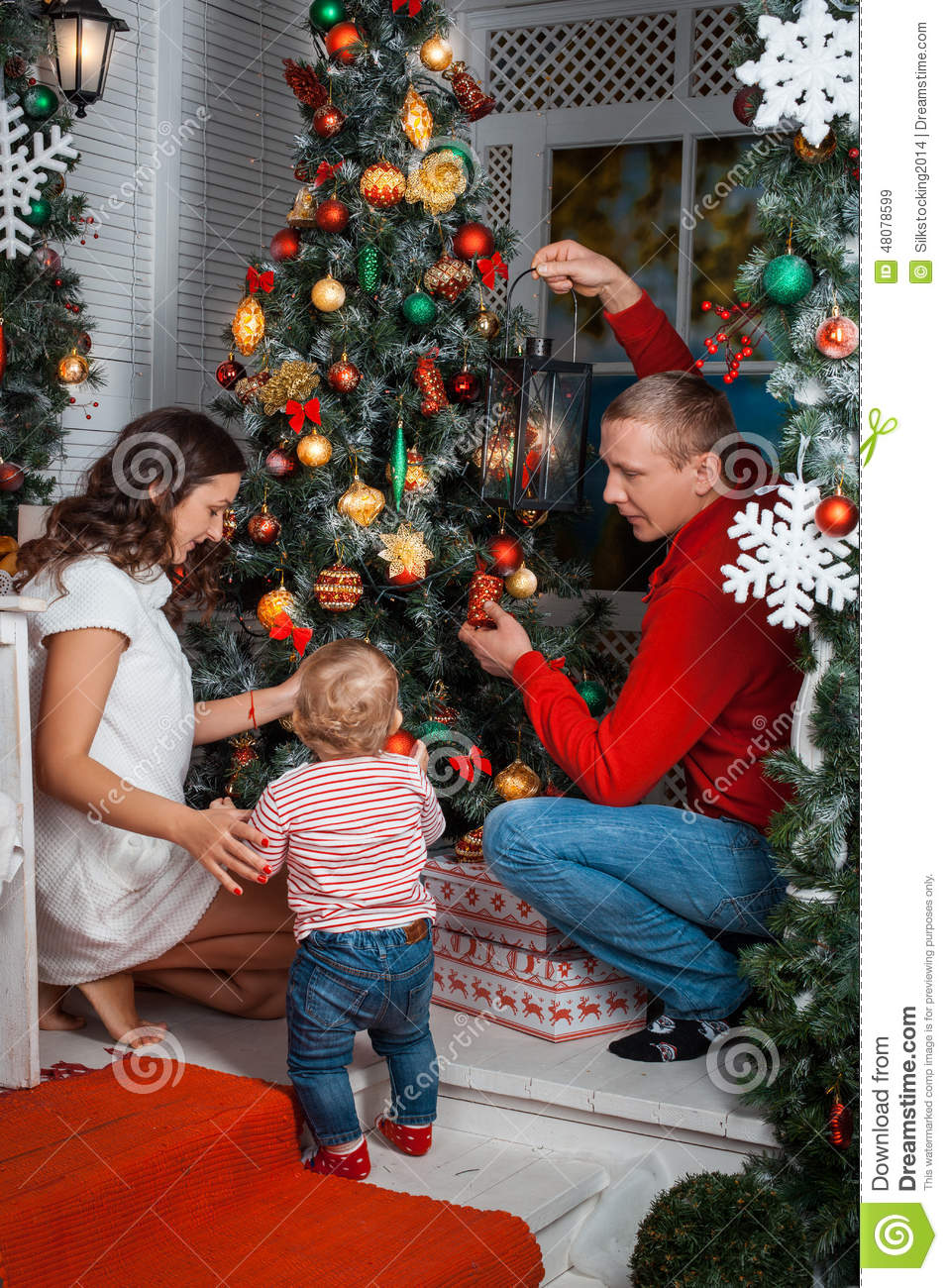 Young Family Decorating A Christmas Tree Stock Photo