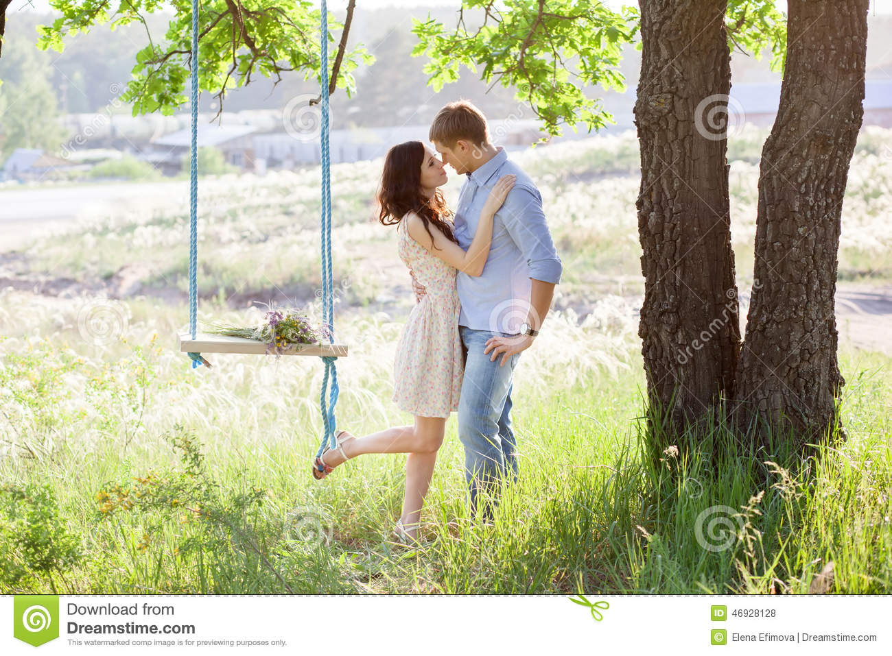Young Kissing Couple Under Big Tree With Swing Stock Photo