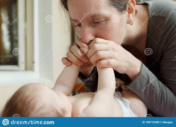 Young Mother Kissing The Tiny Feet Of Her Baby Stock Photo ...