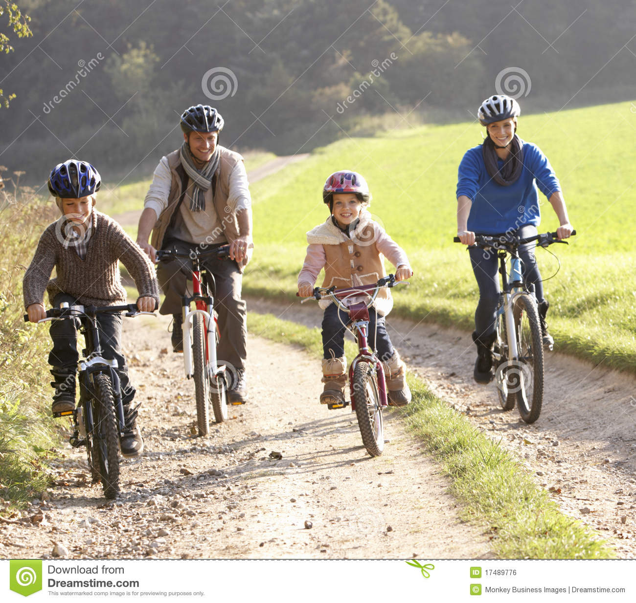 Young Parents With Children Ride Bikes In Park Royalty