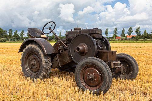 Historische tractor op een stoppelveld
