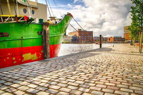 Groen en rood schip aan de kade