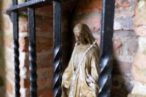 Mariabeeld achter tralies